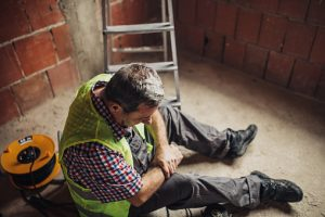 An injured construction worker holding his arm