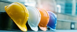 Yellow, white, orange, and blue hard hats in a row.