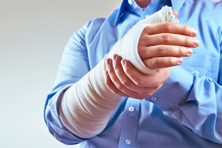 Man in a blue shirt holds his broken wrist with his other hand.