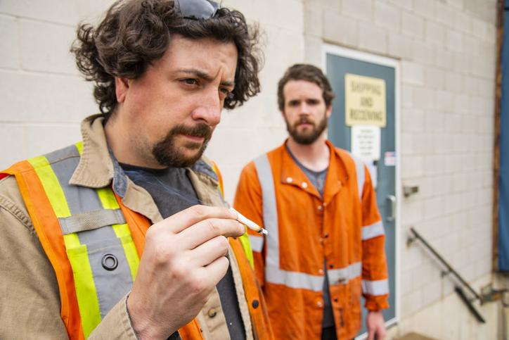 An industrial warehouse employee smoking marijuana
