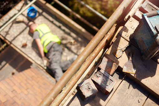 a builder or roofer has fallen from the top elevation of scaffold on a construction site and landed on the next level . He is grimacing in pain . The shot is focussed on the area that the roofer had been working .
