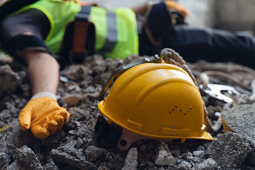 Construction worker has an accident while working on new house. The worker is lying on the ground with his yellow hard hat in the foreground