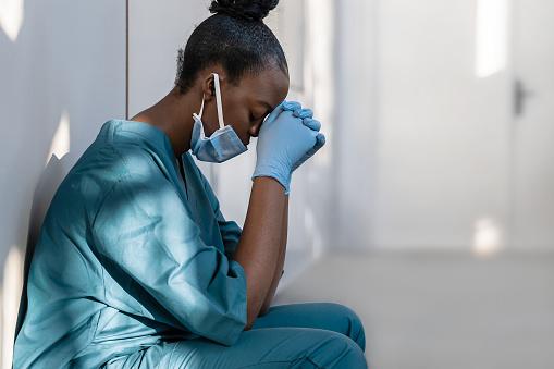 Tired depressed female scrub nurse wears face mask blue uniform gloves sits on hospital floor.