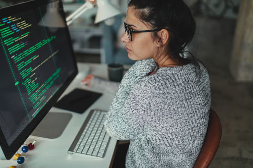 Photo of a young woman sitting at her desktop computer, doing computer programming in her home office